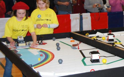 """Two members of the Girl Scouts of Nassau County in Hicksville – Team 2052 """"LEGO Chicks"""" guide their robot on the course at the January 11 Long Island LEGO League Tournament."""